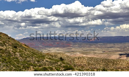 View of red rock mountains in Sedona Arizona with snow capped San Francisco Peaks in Flagstaff Arizona taken from mountaintop in Jerome Arizona
