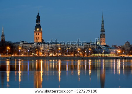 View of Riga (latvia) in evening. Old buildings are illuminated and reflect in the Daugava river.
