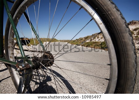 View of road through bike wheel spokes - stock photo
