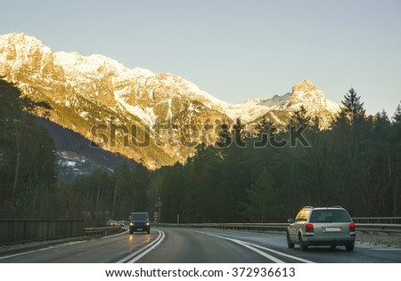 View of road with car at sunset in winter Switzerland. Switzerland is a country in Europe. Switzerland has a high mountain range, from the Alps to Jura mountains.