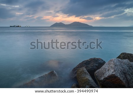 View of rocks, ocean and cloudy sky at the Cheung Chau Island in Hong Kong, China, at sunset.
