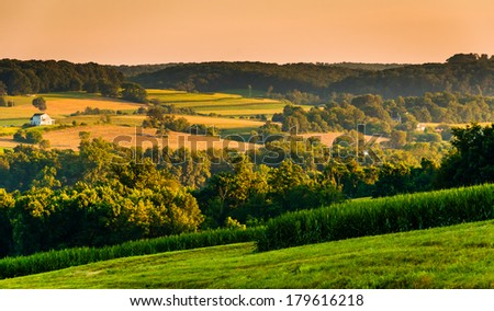 View of rolling hills and farm fields at sunset, in rural York County, Pennsylvania. - stock photo