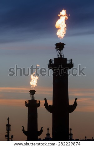 View of rostral column silhouettes with fire during of the City Day celebration in center of Saint Peptersburg city, Russia - stock photo