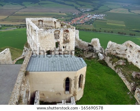 View of ruined palace and partially reconstructed chapel at famous Spis Castle ruin. This castle is included in the UNESCO world heritage list since 1990 and it is popular tourist attraction. - stock photo