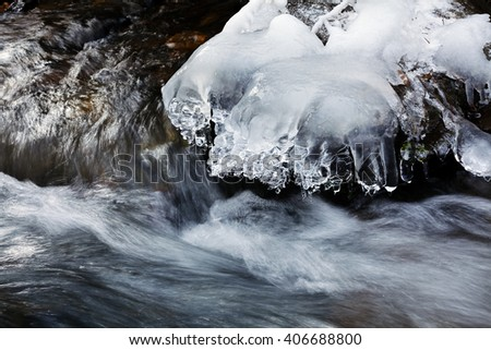 View of running water of small mountain creek and ice on the rocks