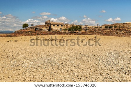 View of rural house in Spain, we see the fields of cereals on a sunny day with clouds, you can see the church of the village - stock photo
