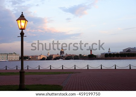 View of Saint Petersburg in Russia across Neva river at sunset with street lamp - stock photo