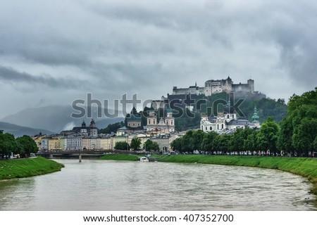 View of Salzburg with Festung Hohensalzburg and Salzach river in rainy summer day, Salzburg, Austria. Salzburg cityscape in a cloudy day. Beautiful Salzburg. Mountain castle, Austria. Austria castle. - stock photo