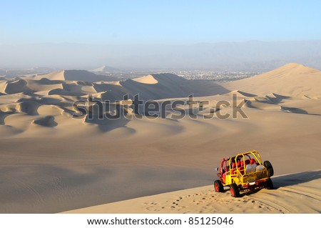 View of Sand Dessert with Dune Buggy in foreground - stock photo