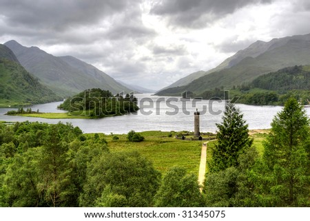 View of Scottish Highland from Glenfinnan with war monument and lakes surrounded by mountains HDR - stock photo
