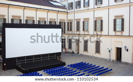 View of screen and Empty blue chairs for outdoor cinema - stock photo