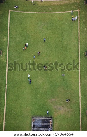 View of section of Champ de Mars from top of Eiffel Tower showing grassy field with tourists walking on rectangular shaped area