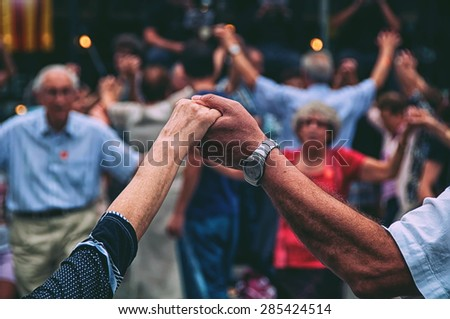 View of senior people holding hands and dancing national dance Sardana at Plaza Nova, Barcelona, Spain. It is a type of circle dance typical of Catalonia. Toned photo - stock photo