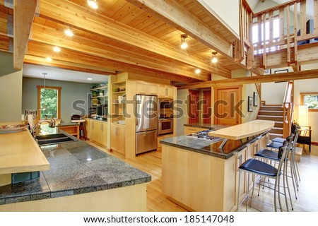 View of shiny kitchen with steel appliances, light wooden cabinets and ceiling beams. View of bar with stools and counter top with sink - stock photo