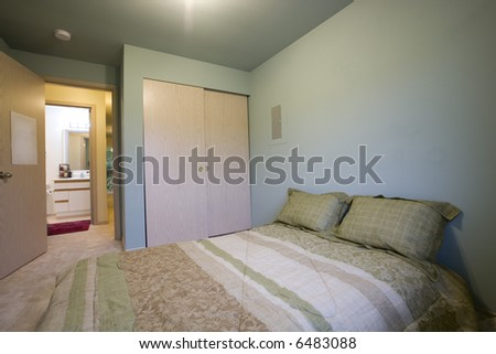 View of simple bedroom with bathroom through door - stock photo