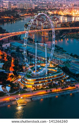 View of Singapore at night with the Singapore Flyer. - stock photo