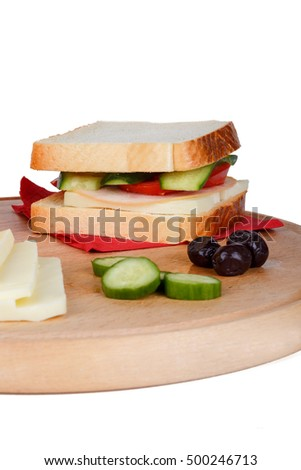 View of slice of bread with cheese, olive and cucumber around, isolated on white background.