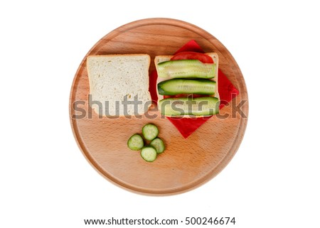 View of slice of bread with tomato and cucumber around, isolated on white background.