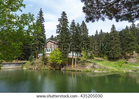 View of small Akgol lake in Ayancik, Sinop around big mountains with high pine trees on cloudy sky background. - stock photo