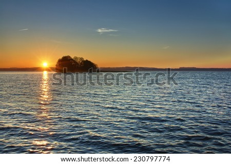 View of small island on a lake during sunrise, Mazury, Poland - stock photo