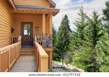 View of small  porch with wooden staircase bridge, siding house exterior.