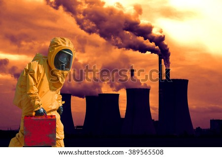 View of smoking coal power plant at sunset and men in protective hazmat suit - stock photo