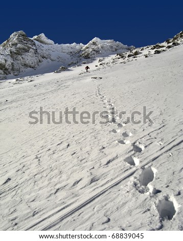 View of snow mountain and hiking man. Slovakian  High Tatra Mountains.