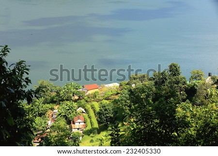 View of some homesteads among orchards on the shore of the 4.43 km2-784 ms.high Phewa tal-lake seen from the way down Ananda Hill and opposite Pokhara city. Kaski district-Gandaki zone-Nepal.  - stock photo