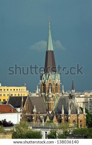 View of St Lazarus Church among the roofs of Vienna with stormy clouds, Austria - stock photo