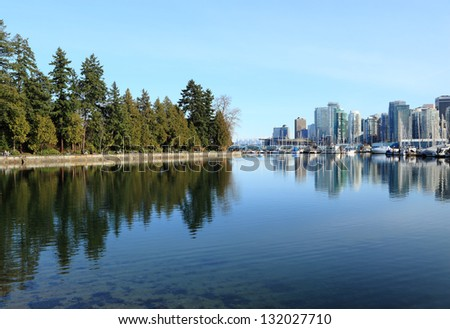 View of Stanley Park juxtaposed by a view of downtown Vancouver - stock photo