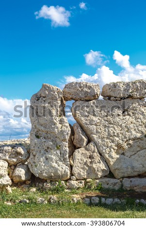 View of stone structures of ancient Ggantija Temples in Gozo Malta, on cloudy blue sky background.