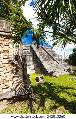 View of stoned wall and Chichen Itza monument, Mexico surrounded by palms in summer - stock photo