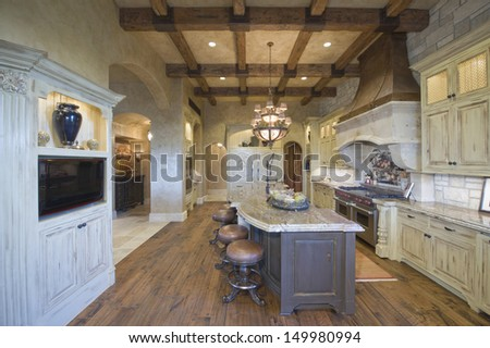 View of stools at island with chandelier and wood beamed ceiling in kitchen - stock photo