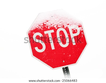 View of stop sign partially covered in snow during a snowstorm. - stock photo