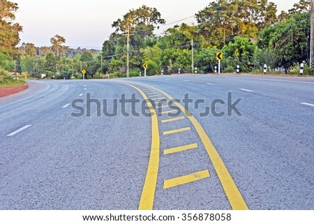 view of suburban curved asphalt road - day time Large curving highway in rural area on cloudy sky. - stock photo
