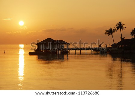 View of sunrise behind a pier in Indian Ocean, Maldives - stock photo