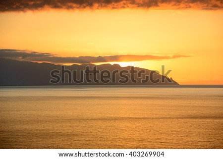 View of sunset in the clouds over Gomera Island from Los Gigantes, Tenerife, Canary Islands, Spain.