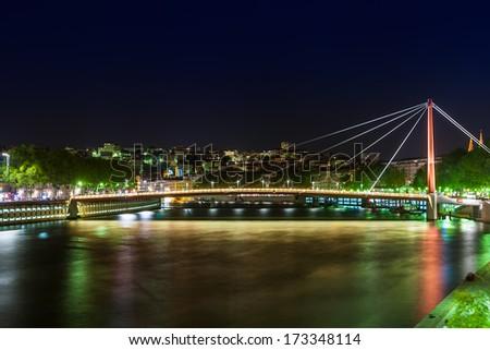 View of Suspension Bridge (Passerelle du Palais de Justice), Saone River at night, Lyon, France - stock photo