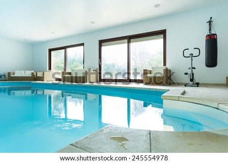 View of swimming pool inside expensive house - stock photo