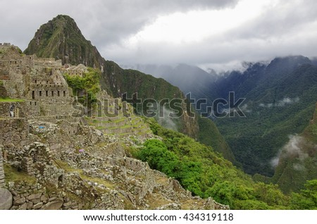 View of temple ruins and terrace in Lost Inca City of Machu Picchu. Low clouds and mountains at background. Cusco Region,Sacred Valley, Peru - stock photo