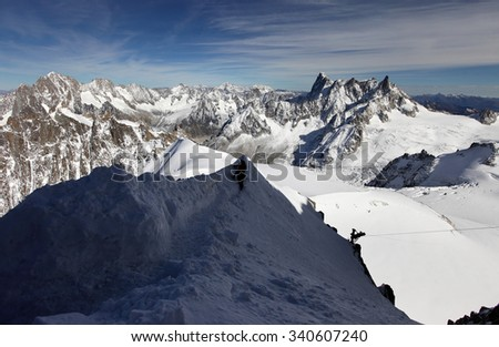 View of the Alps from Aiguille du Midi mountain in the Mont Blanc massif in the French Alps. Summit tourist station in foreground.Peaks in snow and glacier of Mont Blanc Alps, France, Europe. - stock photo