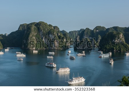 View of the amazing limestone karsts in Ha Long Bay, Vietnam. Thousands of karst hills on the waters deliver an amazing view. Tourist boats are seen sailing on the water. - stock photo