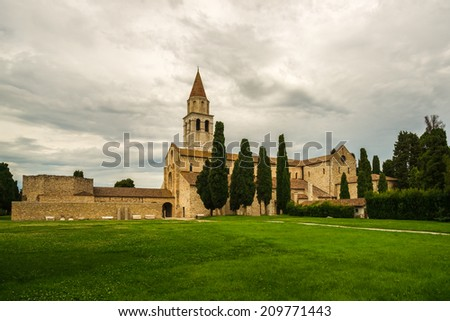View of the ancient Basilica di Santa Maria Assunta in Aquileia against a blue sky