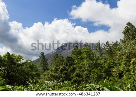 View of the Arenal Volcano in the clouds with dense green vegetation in the foreground