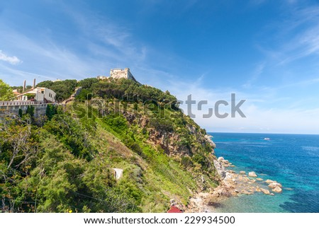 View of the bay and old fortress on a rock, Tuscany, Italy. - stock photo