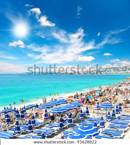 View of the beach in Nice, France, near the Promenade des Anglais, full with tourists, sunbeds and umbrellas on summer hot day - stock photo