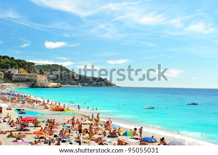 View of the beach in Nice, France, near the Promenade des Anglais. tourists, sunbeds and umbrellas on summer hot day - stock photo