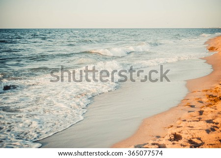 view of the beach sand with sea waves and white foam filter - stock photo