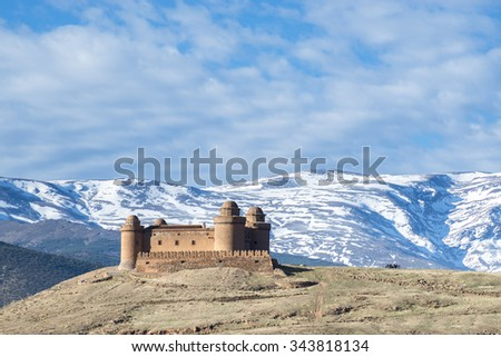 View of the castle  Calahorra with the snow capped mountains of the Sierra Nevada, La Calahorra, Gaudix, Granada Province, Andalusia, Spain. - stock photo
