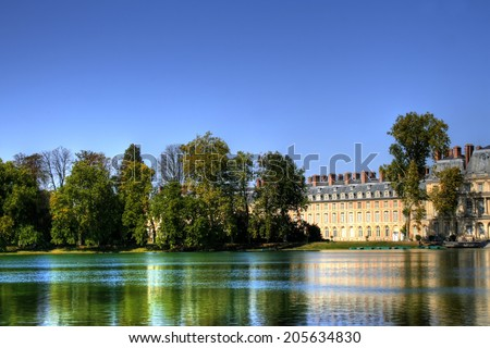 View of the Chateau de Fontainebleau and its reflection across a tranquil lake, situated close to Paris it introduced the Mannerist style of architecture to France and is the largest royal chateau - stock photo